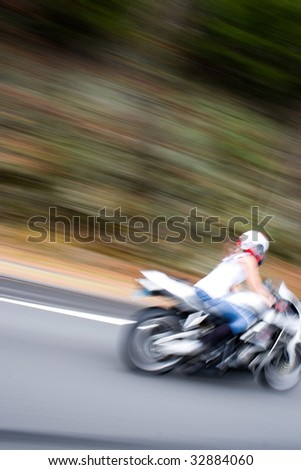 Abstract blur of a pretty girl driving a motorcycle at highway speeds.  Intentional motion blur. - stock photo
