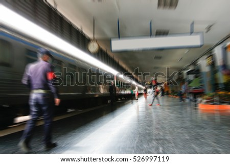 abstract blur of train station with passenger about to leave while the next train waits to come in.