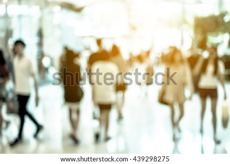 Abstract blur people walking in fashion mall. Sunlight shining through windows in summer. Cold color filter. - stock photo