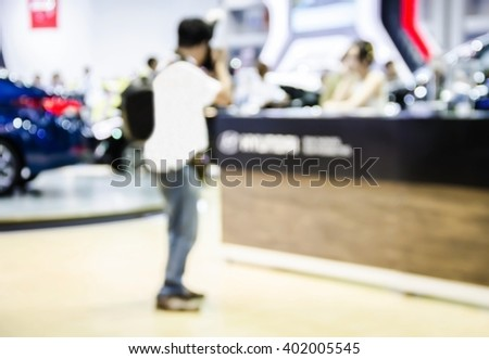 abstract blur photographers shooting a woman in motor show exhibition.