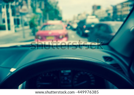 Abstract blur traffic from inside car view background - Vintage filter effect, Selective focus on steering wheel - stock photo