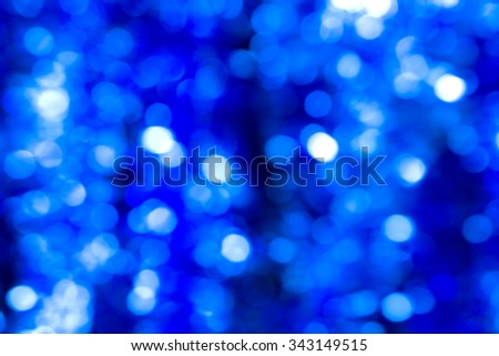 Abstract blured background of blue contrasted dark shiny Christmas tree decorations