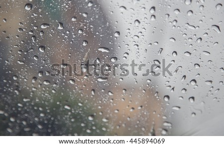 Abstract blurred background of drops of rain on mirror car