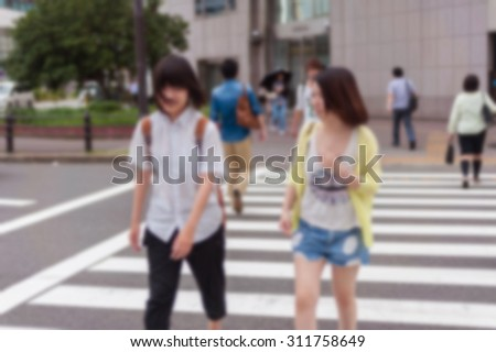abstract blurred background  People walk across the crosswalk On the street in Osaka, Japan. - stock photo
