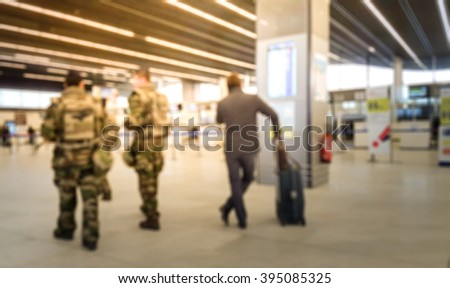 Abstract blurred background : Soldiers on patrol in airport terminal or train station against terrorism. Airline passenger with luggage watch a flight information board. Security, terrorism concept