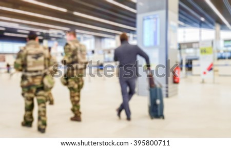 Abstract blurred background : Soldiers on patrol in airport terminal or train station against terrorism. Airline passenger with luggage watch a flight information board. Security, terrorism concept  - stock photo