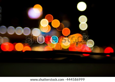 Abstract blurred bokeh colorful  image of people driving car on night time for background usage.(take photo from inside)