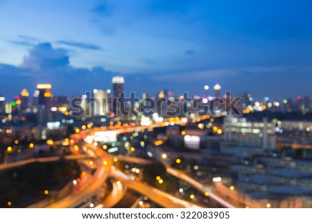 Abstract blurred bokeh light, freeway intersection with city background during twilight - stock photo
