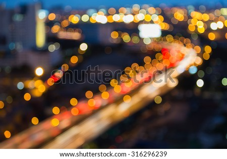 Abstract blurred bokeh light of City highway curved at night - stock photo