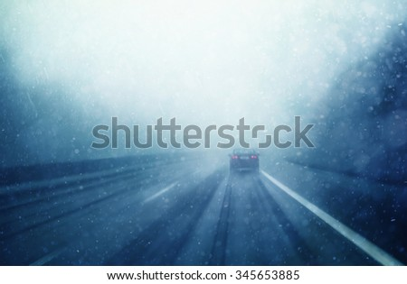 Abstract blurred car dangerous highway driving in heavy snowfall and rainfall. Winter snowy conditions on the highway. Motion blur visualizes the speed and dynamics. - stock photo
