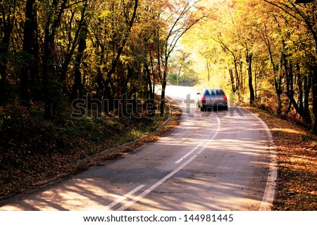 abstract blurred car in autumn forest road - stock photo