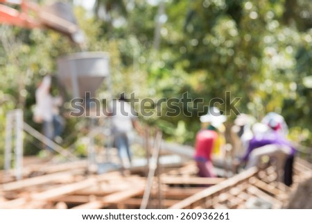 Abstract blurred construction building workers at a construction site are pouring concrete  - stock photo