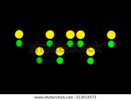 abstract blurred green and yellow LED flashing circles on a black background