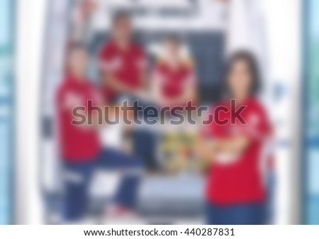 Abstract blurred group of emergency medical service team in front of ambulance - stock photo