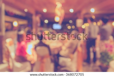 Abstract blurred image of Large dining table set for wedding, dinner or festival event with beautiful lights decoration inside large hall for background usage . (vintage tone) - stock photo