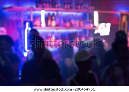 Abstract blurred image of people crowding the bar in a nightclub - stock photo