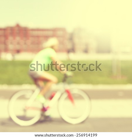 Abstract blurred image of woman on bicycle in the city. - stock photo