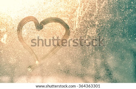 Abstract blurred love heart symbol drawn by hand on the wet, frozen and dirty window glass with yellow gold sunlight background. Selective focus used. - stock photo