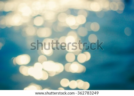 abstract blurred of surface water background in vintage warm tone color:blurry bokeh circle light motion on calmness river backdrop with vignette:defocus of ocean display picture:blur aqua concept. - stock photo