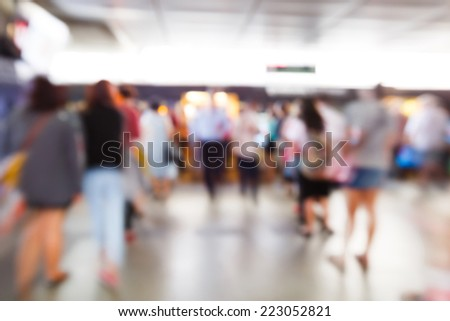 Abstract blurred people walking or standing in electrical train station - stock photo