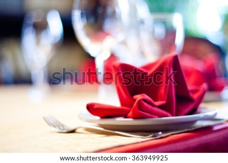 Abstract blurred served table. Romantic restaurant interior with tablecloth, napkins, wine glasses and cutlery. colorful still life and service concept photography - stock photo
