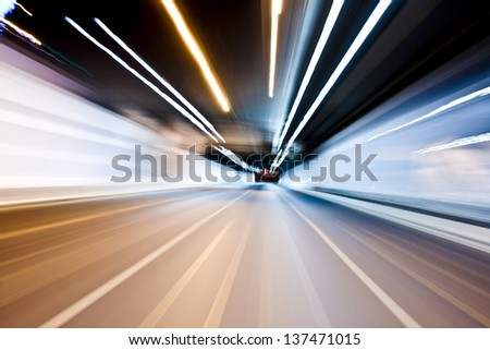 Abstract blurred speed motion in urban highway road tunnel, moving toward the light - stock photo