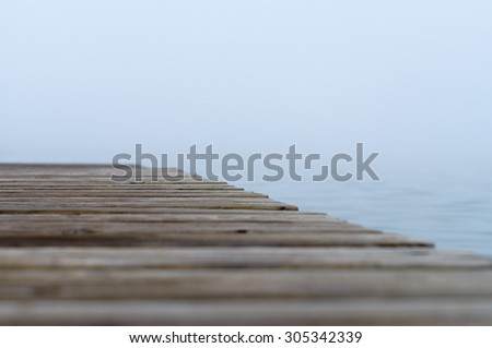 Abstract blurred view of misty lake with selective focus on wooden pier - stock photo