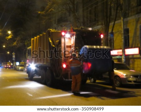 Abstract blurred Worker of municipal recycling garbage collector truck loading waste and trash bin. Night Scene. Great background