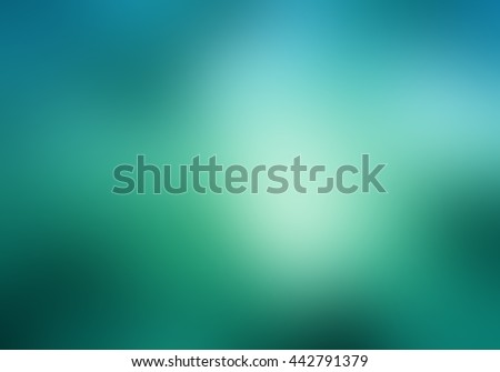 abstract blurry blue green sky background with bright light leak bokeh or sunspot flare, abstract smooth textured bright white shiny center spot on blurred teal background