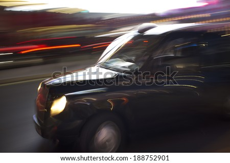 Abstract blurry image of a London taxi cab driving on a street. - stock photo