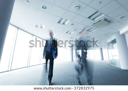 Abstract blurry portrait of walking businessman in office
