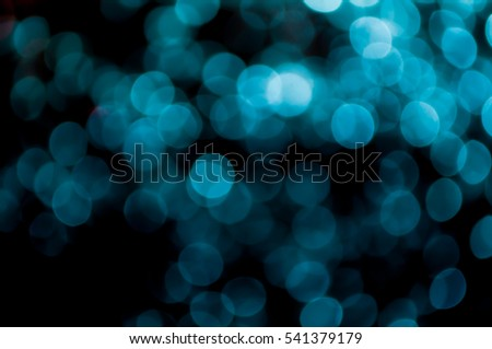 Abstract bokeh light blue and black colors defocused circular background. Christmas light or season greeting background.