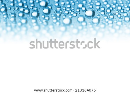 Abstract Border of Blue Water Drops - soft focus on the center, copy space for text - stock photo