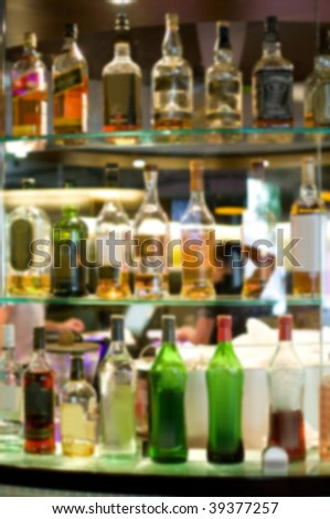 Abstract bottles of spirits and liquor at the bar (blurred image) - stock photo