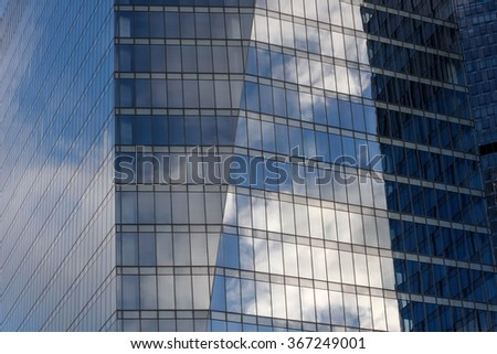 Abstract building background of a modern office building of glass and steel with reflection of the sky on its surface