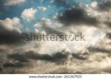 Abstract busy dark cloud over vibrant color sky background - stock photo