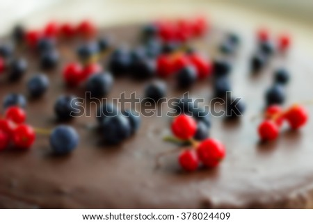 Abstract cake blurred background with beautiful bokeh. Defocused cake background with berries. Blur image chocolate cake. Chocolate cake. Fresh berries. Chocolate glaze.  - stock photo