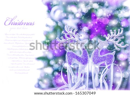 Abstract Christmas border, small glass reindeer decor in champagne glasses, Xmas tree with purple decoration, text space, greeting cars with congratulation - stock photo