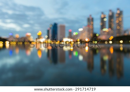 Abstract city bokeh lights during blue hours, with water reflection - stock photo