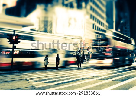 Abstract cityscape blurred background, art toning. Night view of modern city street with moving transport, illuminated skyscrapers and walking people. Hong Kong - stock photo
