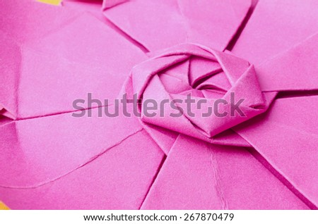 Abstract closeup of the intricate central radial part of a pink paper origami flower. Side view.