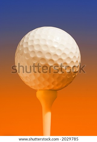 Abstract closeup of white golfball on tee with orange and blue lighting effect - stock photo