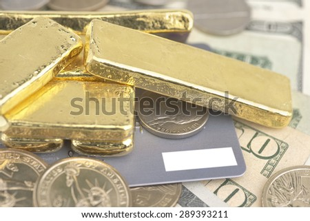 Abstract closeup pile of gold bars over dollar coins, banknotes and credit card - stock photo