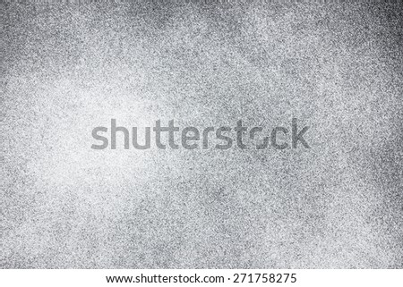 Abstract closeup white spray paint on black paper. - stock photo