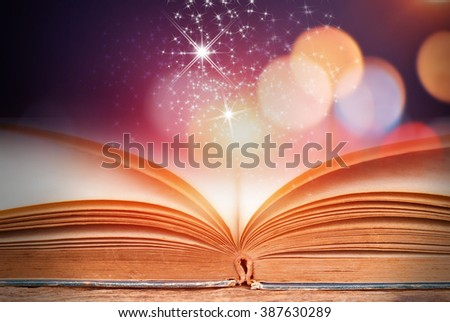 Abstract colorful magic book on wooden background