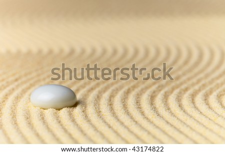 Abstract composition - a sandy yellow background and a glass stone