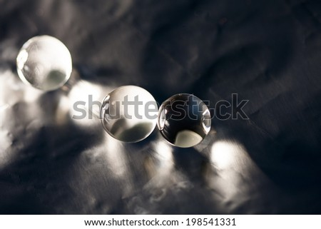Abstract composition with beautiful, transparent, round jelly balls on an aluminum foil with reflections and dark background  - stock photo