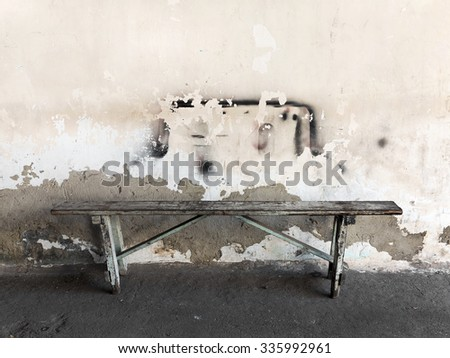 Abstract concrete, weathered with cracks and scratches. Landscape style wooden bench standing at the wall. Grungy concrete surface. Great background or texture. - stock photo