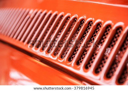 Abstract cooling grill detail of a red vintage car - stock photo