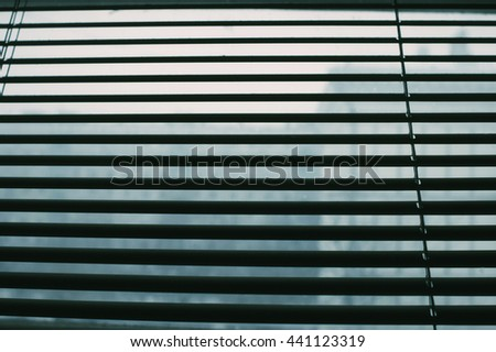Abstract dark background with closed blinds closeup - stock photo